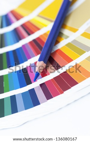 choosing the color from the spectrum - open pantone color card with blue pencil - stock photo