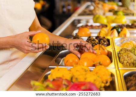 Choosing the freshest fruits. Close-up of woman choosing fruits in grocery store  - stock photo