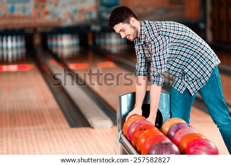Choosing the lucky ball. Cheerful young man choosing bowling ball and smiling while standing against bowling alleys - stock photo