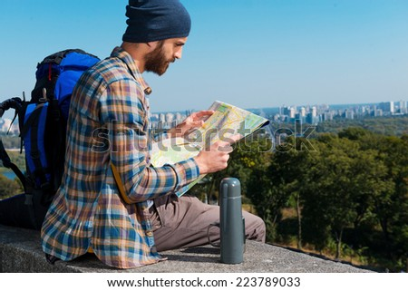Choosing the next route . Concentrated young man sitting near backpack and looking through a map   - stock photo