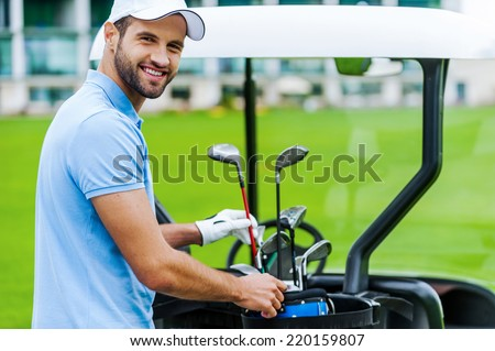 Choosing the proper driver. Handsome young male golfer choosing driver while standing near the golf cart  - stock photo