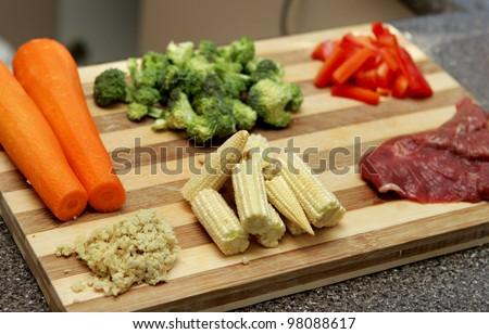 chopped and prepared stir fry ingredients including steak and vegetables - stock photo