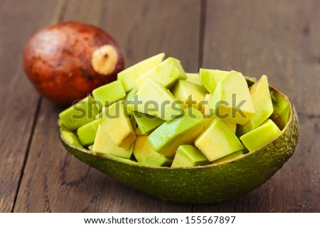 Chopped Avocado fruit with core on brown wooden old table. - stock photo
