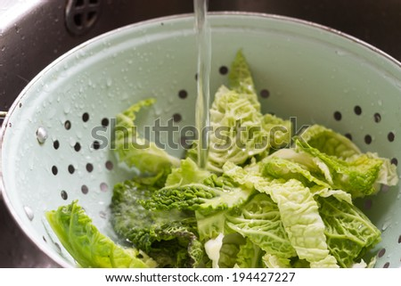 Chopped cabbage in a colander, being washed under running water. - stock photo