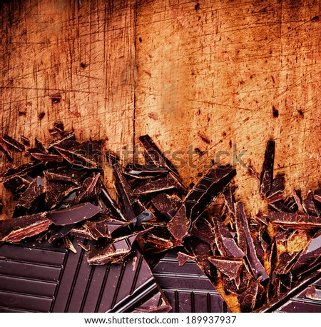 Chopped Chocolate Bar on wooden background closeup. Broken dark chocolate bar on wood table macro. - stock photo
