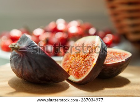 Chopped Fig fruit on the cutting board with briar (dog rose) on the plate - stock photo