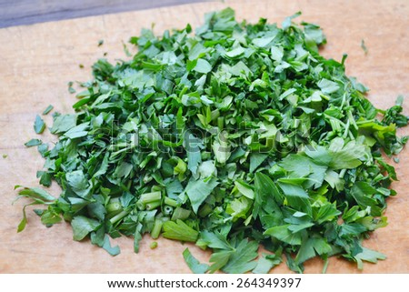 Chopped fresh green parsley on wooden board - stock photo