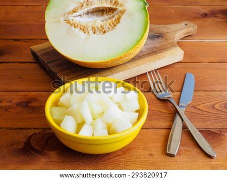 Chopped fresh melon in a yellow bowl - stock photo
