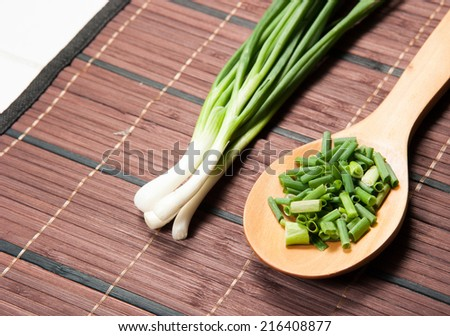 Chopped green  onions and spoon on a wooden mat - stock photo