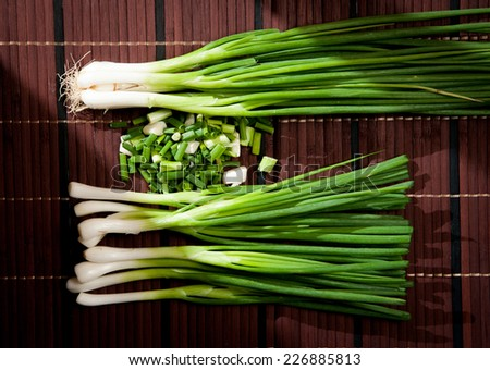 Chopped green onions on a wooden - stock photo