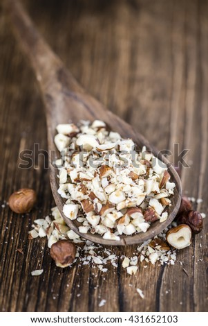 Chopped Hazelnuts (selective focus) on vintage background (close-up shot) - stock photo