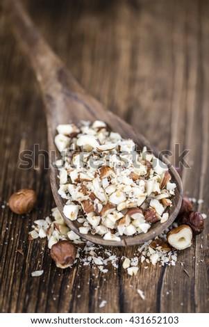 Chopped Hazelnuts (selective focus) on vintage background (close-up shot) - stock photo