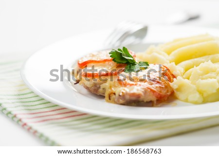 Chopped meat with smashed potato on white plate - stock photo