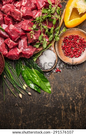 Chopped raw meat with vegetables, herb and spices for goulash on  rustic wooden background, top view, place for text - stock photo