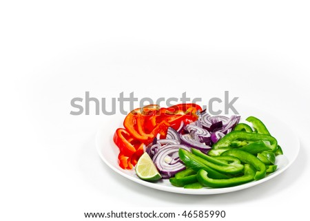 Chopped red and green peppers on a white plate with a chopped red onion. Isolated on a white background, with lots of copyspace. - stock photo
