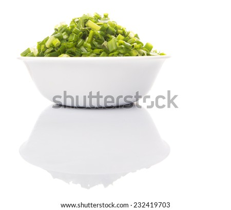 Chopped scallion or spring onion leaves in a white bowl - stock photo