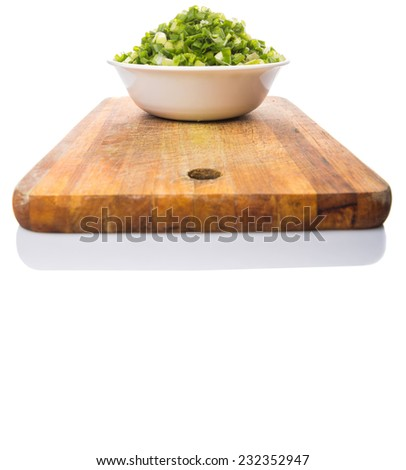 Chopped scallion or spring onion leaves in a white bowl on a wooden cutting board - stock photo