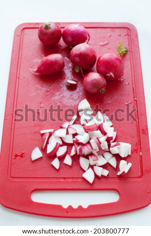 Chopped vegetables radish on background of red chopping board, isolated on white - stock photo