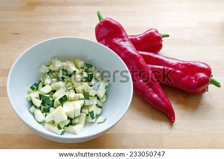 chopped zucchini in a white bowl and three red sweet pointy peppers (capsicum) on a wooden board, cooking preparation - stock photo