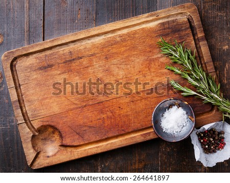 Chopping board, seasonings and rosemary on dark wooden background - stock photo