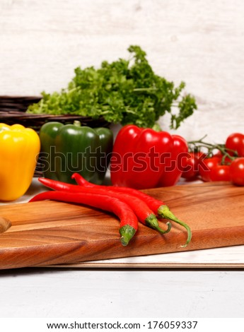 Chopping board with paprika and chilli - stock photo