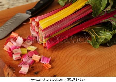 Chopping rainbow swiss chard in a modern kitchen - stock photo