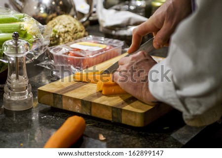 Chopping vegetables on a cutting board in the kitchen - stock photo