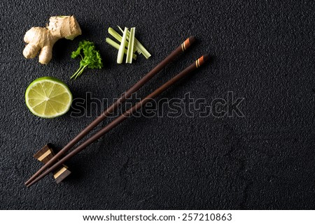 Chopsticks and food ingredients on black stone table top view - stock photo