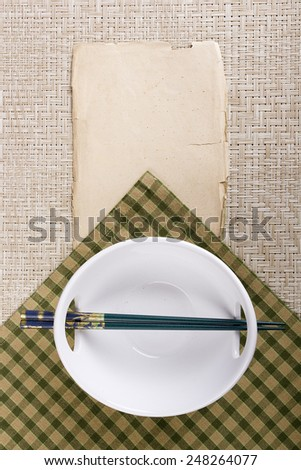 Chopsticks and plate in oriental style on cloth bedding. - stock photo