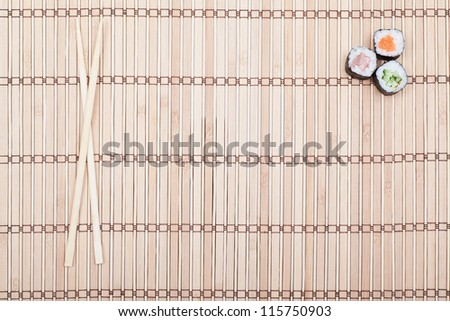 chopsticks and sushi roll on bamboo mat. background menu - stock photo