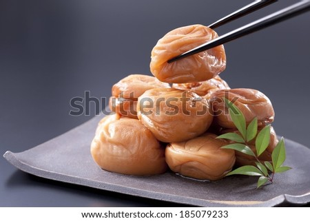 Chopsticks lifting a piece of food from a tray of food. - stock photo