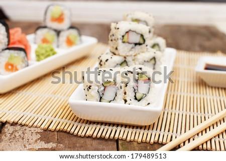 Chopsticks next to a set of asian sushi - stock photo