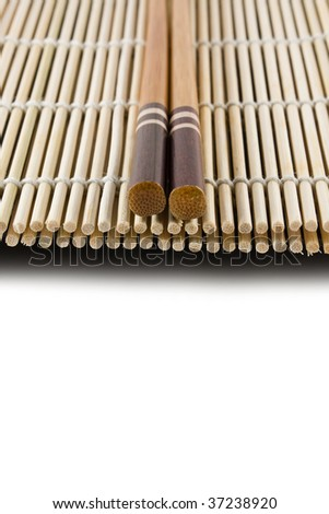 Chopsticks on a Japanese sushi rolling mat - stock photo