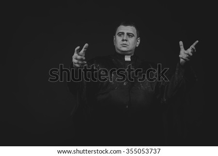 Chorno white photography priest on a dark background. Emotional Photos religious rights. Photo for religious magazines and websites. - stock photo
