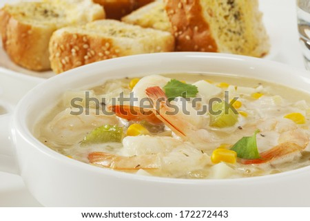 Chowder - with shrimp or prawns, corn, potatoes and coriander, served with garlic bread. - stock photo