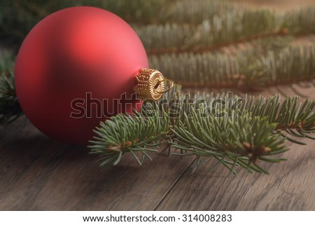 chrismas ball on wood table with spruce, vintage toned photo - stock photo