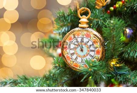 Christamas tree decoration with clock showing five minutes left to new year - stock photo