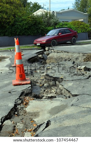CHRISTCHURCH, NEW ZEALAND - FEBRUARY 24: Car falls into a crack caused by the largest and most devastating earthquake Christchurch has experienced on February 24, 2011 in Christchurch. - stock photo