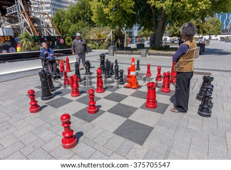 CHRISTCHURCH, NEW ZEALAND - FEBRUARY 10, 2016: Disabled man plays big chess on the sidewalk. - stock photo