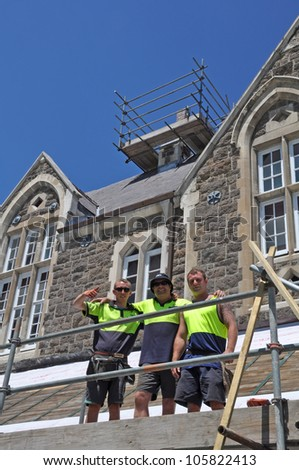 CHRISTCHURCH, NEW ZEALAND - JANUARY 14: A team of three happy builders are re-tiling the damaged roofs of earthquake damaged houses at Christs College on January 14, 2011 in Christchurch. - stock photo