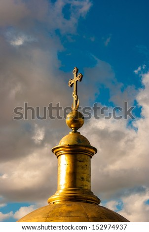 christian cross against blue cloudy skies - stock photo