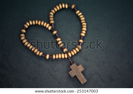 Christian cross necklace on Holy Bible book, Jesus religion concept as good friday or easter festival in heart shape - stock photo