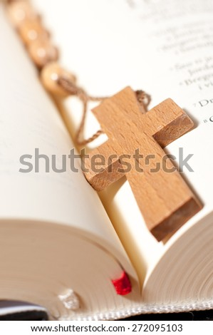 Christian cross necklace on open Bible. - stock photo