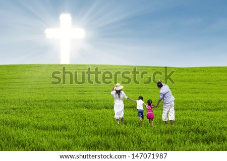 Christian family having fun on green field with cross symbol - stock photo