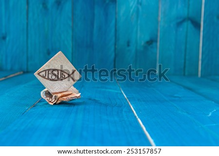 Christian fish symbol carved in wood on white vintage wooden background - stock photo