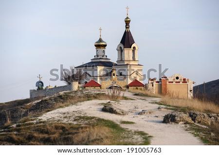 Christian Orthodox church in Old Orhei, Moldova, in rays of sunset - stock photo