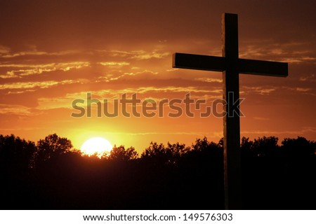 Christian Photo illustration of a Dramatic Sky with Large wooden Cross standing against very saturated colors of bright yellow sun, rich orange clouds, sunlight shafts, and silhouetted trees. - stock photo