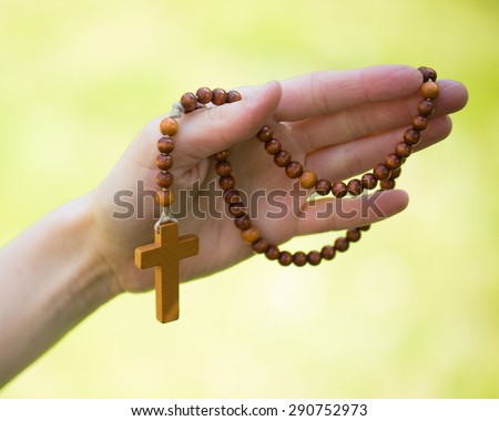 Christian prayer beads and crucifix in the hand of woman  - stock photo