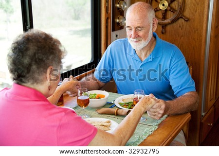 Christian senior couple in their motor home, saying grace over their meal. - stock photo