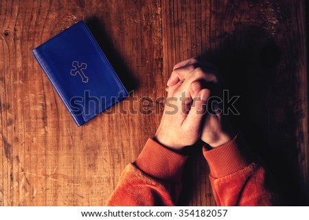 Christian woman praying with hands crossed and Holy Bible by her side on wooden desk in church, top view,s elective focus - stock photo
